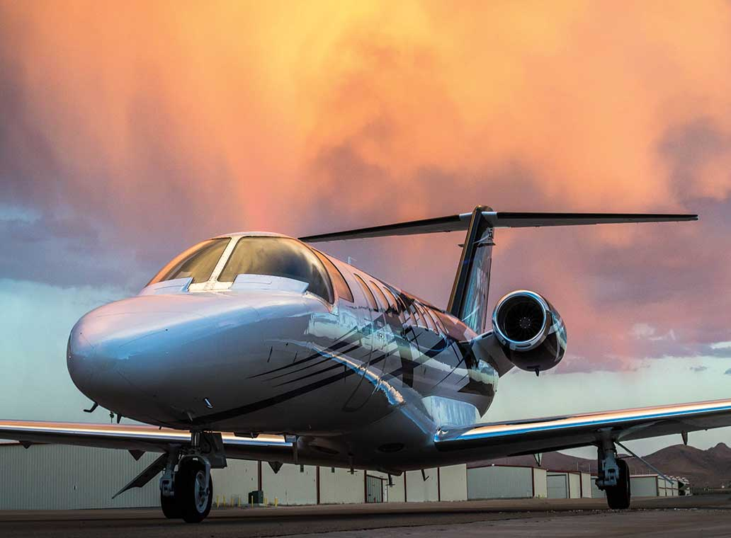A private jet on the tarmac at sunset